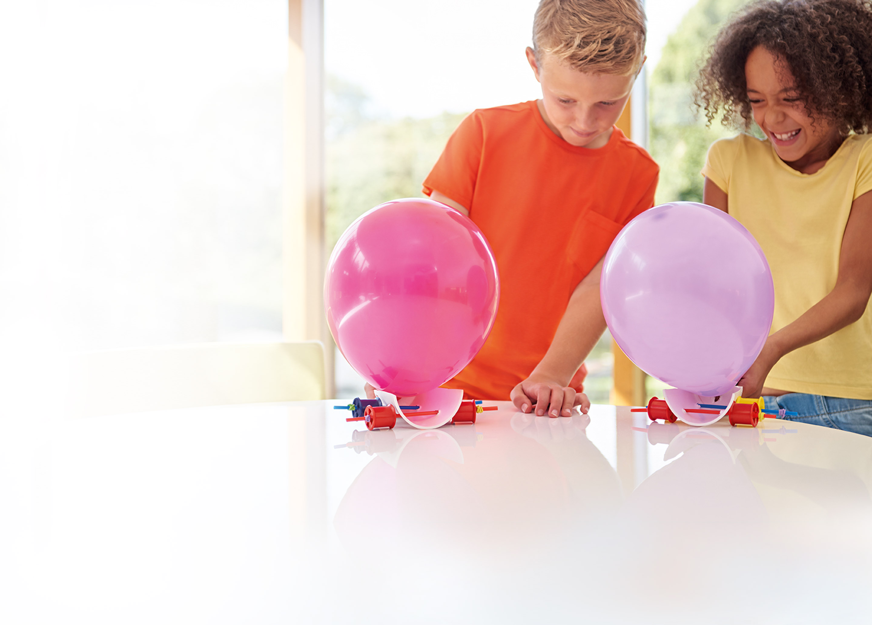 Two children racing the balloon cars they have made from a James Dyson Foundation challenge card.