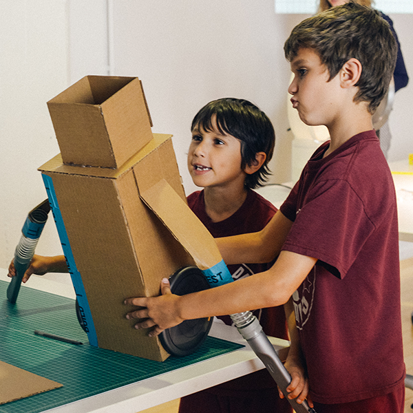 Two young boys with their prototype made from cardboard and Dyson vacuum cleaner parts.