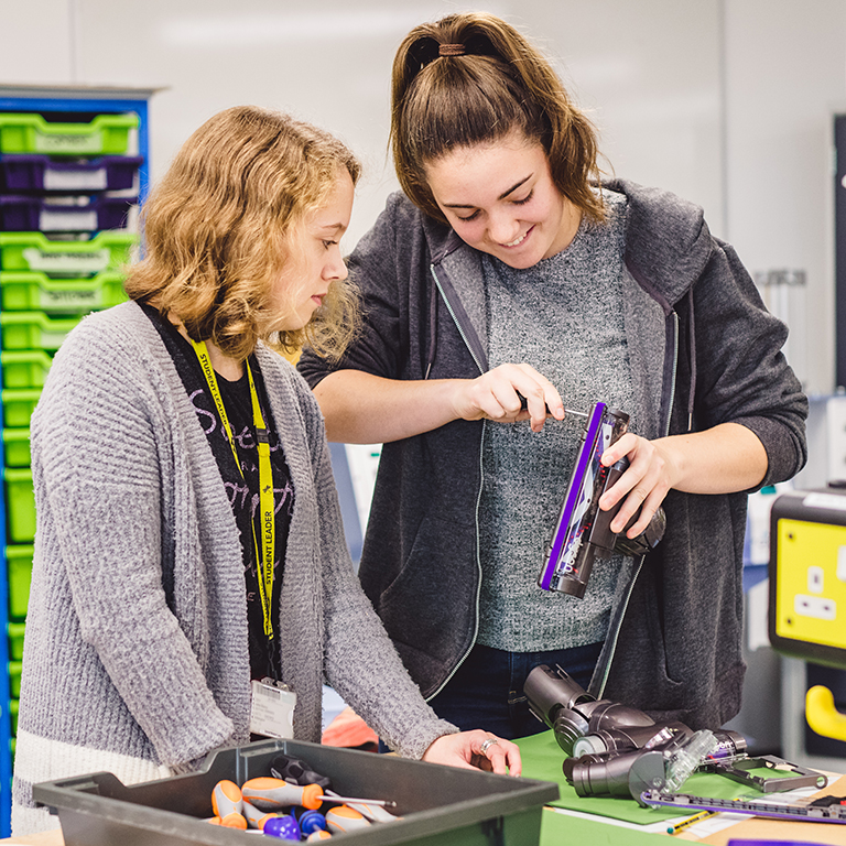 Two female students taking apart a Dyson vacuum cleaner head with a screwdriver.
